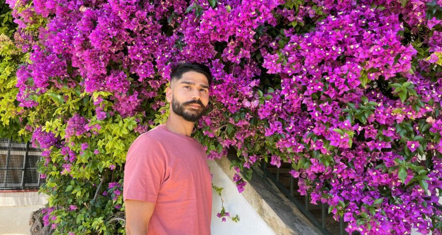 Photo of Taimour standing in front of purple flowers in a peach colour tshirt